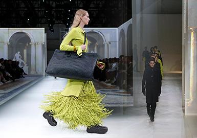 """有著""""意大利愛馬仕""""之稱的Bottega Veneta,自信、優雅而忠于自己風格是其品牌風格。2019 年末,新任的創意總監Daniel Lee 帶領的BV團隊 ,橫掃了英國時尚大獎,使其成為本屆米蘭時裝周最值得關注的大秀之一。Bottega Veneta 20/21年秋冬系列在米蘭發布,秀場運用投影技術,用燈光投影裝置再現了文藝復興時期意大利建筑大師 Andrea Palladio 的建筑風格。BV新系列不再是肅穆的色調,用充滿明快的奇異果綠色彩等熒光色系,打造未來標識性的色彩。Daniel Lee 用 59 個 look 表現女性潛藏在柔軟下的自信,展現純粹的自我表達,塑造出充滿知性氣息的都市風格。同時本次秀場裝置用的材料都是可重復使用與可回收的,后臺的餐飲也使用可降解餐具、有機食材,剩余食物會捐獻給ONG 組織,打造完全環保和最大限度減少浪費的時尚態度!"""